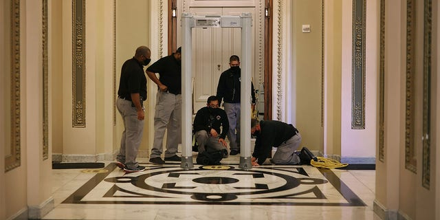 WASHINGTON, DC - JANUARY 12: U.S. Capitol Police install a metal detector outside the House of Representatives Chamber, on the very spot where less than a week earlier violent insurrectionists attempted to smash their way through and halt the certification of the Electoral College votes, January 12, 2021 in Washington, DC. At the direction of President Donald Trump, the mob attacked the U.S. Capitol on January 6 and security has been tightened ahead of next week's presidential inauguration. (Photo by Chip Somodevilla/Getty Images)