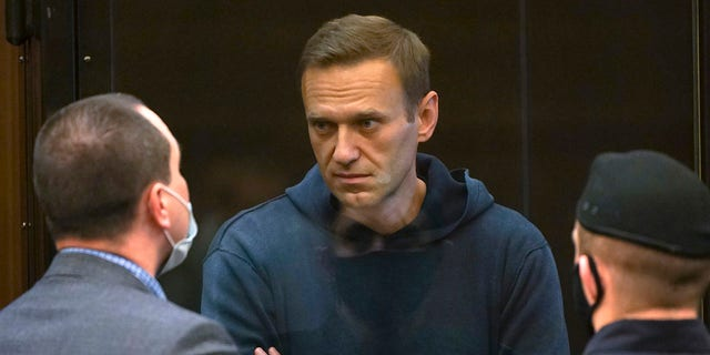 In this handout photo provided by Moscow City Court Russian opposition leader Alexei Navalny talks to one of his lawyers, left, while standing in the cage during a hearing to a motion from the Russian prison service to convert the suspended sentence of Navalny from the 2014 criminal conviction into a real prison term in the Moscow City Court in Moscow, Russia, Tuesday, Feb. 2, 2021. (Moscow City Court via AP)