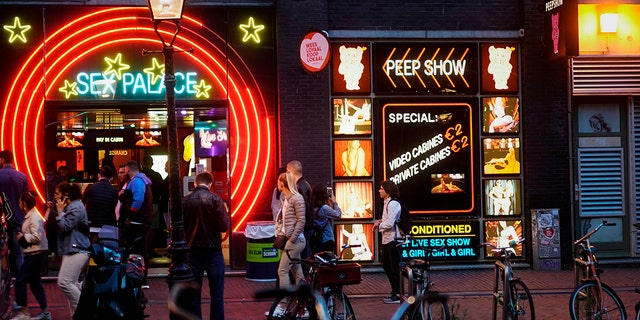 Visitors crowd the red-light district in Amsterdaym after Dutch brothels were allowed to reopen in July following coronavirus shutdowns.