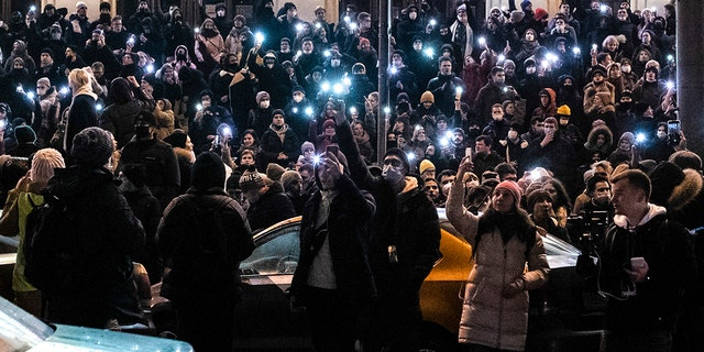 A crowd shine their cellphone flashlights during a protest against the jailing of opposition leader Alexei Navalny in Moscow, Russia, Saturday, Jan. 23, 2021. When the team of jailed Russia opposition leader Alexei Navalny announced a protest in a new format, urging people to come out to their residential courtyards on Sunday and shine their cellphone flashlights, many responded with jokes and skepticism. (Evgeny Feldman/Meduza via AP)