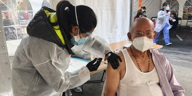 Victor Villegas, 78, right, receives a COVID-19 vaccine shot from a health care worker at a vaccination site in the Mission district of San Francisco, Monday, Feb. 8, 2021. Counties in California and other places in the U.S. are trying to ensure they vaccinate people in largely Black, Latino and working-class communities that have borne the brunt of the coronavirus pandemic. San Francisco is reserving some vaccines for seniors in the two ZIP codes hit hardest by the pandemic. (AP Photo/Haven Daley)