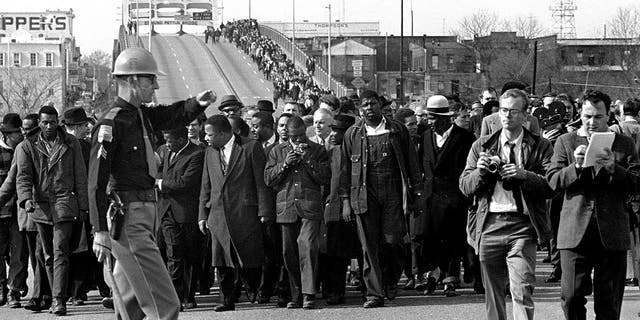 In this March 10, 1965, file photo, demonstrators, including Dr. Martin Luther King, Jr., stream over an Alabama River bridge at the city limits of Selma, Ala., during a voter rights march. King's participation in the 54-mile march from Selma, Ala., to the state capital of Montgomery elevated awareness about the troubles blacks faced in registering to vote. (AP Photo/File)