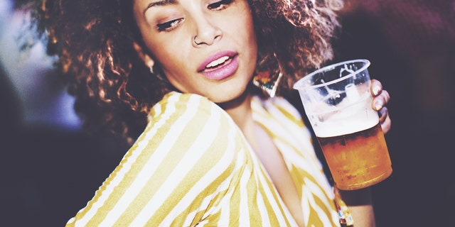 Closeup of an attractive mixed race woman dancing at a party while holding a cup of beer and looking sideways.