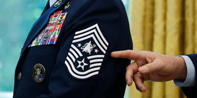 FILE - In this May 15, 2020, file photo, Chief Master Sgt. Roger Towberman displays his insignia during a presentation of the United States Space Force flag in the Oval Office of the White House in Washington. (AP Photo/Alex Brandon, File)
