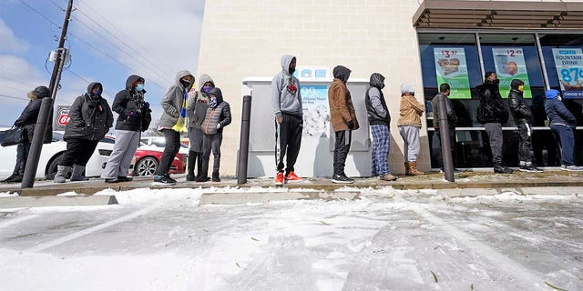 People wait in line to purchase groceries Monday, Feb. 15, 2021, in Houston.