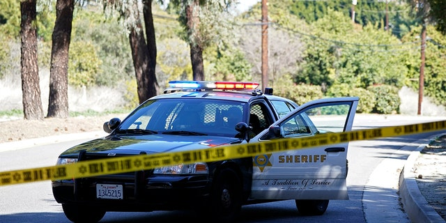 """A police car blocks a road near a rollover accident involving golfer Tiger Woods Tuesday, Feb. 23 in the Rancho Palos Verdes section of Los Angeles. Woods had to be extricated from the vehicle with the """"jaws of life"""" tools, the Los Angeles County Sheriff's Department said in a statement."""