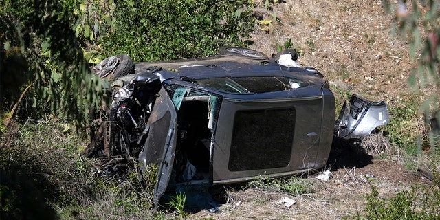 A vehicle rests on its side after a rollover accident involving golfer Tiger Woods along a road in the Rancho Palos Verdes section of Los Angeles on Tuesday, Feb. 23, 2021. Woods suffered leg injuries in the one-car crash. (AP Photo/Ringo H.W. Chiu)