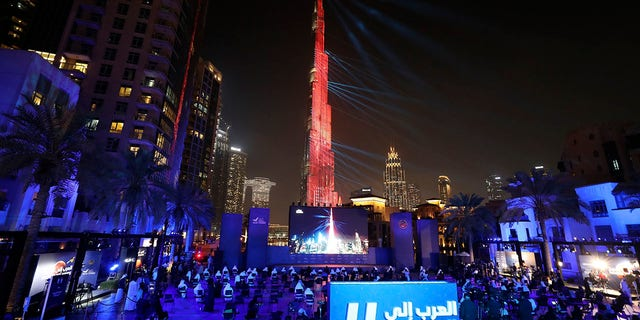 The world tallest tower, Burj Khalifa is lit up with a laser show to celebrate the Hope Probe entering Mars orbit as a part of the Emirates Mars mission, in Dubai, United Arab Emirates, Tuesday, Feb. 9, 2021. The spacecraft from the UAE swung into orbit around Mars in a triumph for the Arab world's first interplanetary mission. It is the first of three robotic explorers arriving at the red planet over the next week and a half. (AP Photo/Kamran Jebreili)