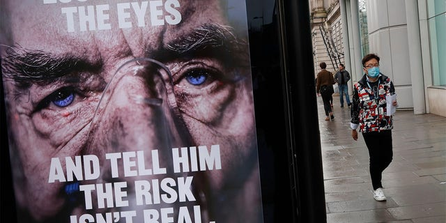 A man wearing a mask against coronavirus walks past an NHS advertisement about COVID-19 in London, Tuesday, Feb. 2, 2021.? (AP Photo/Alastair Grant)
