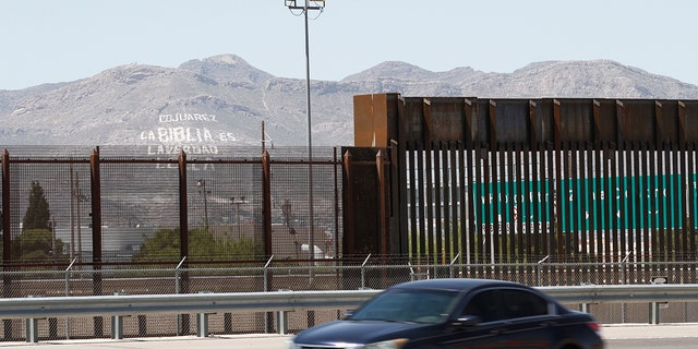 FILE - In this April 22, 2020, photo, a car drives on a highway parallel to a border fence in El Paso, Texas. (AP Photo/Cedar Attanasio, File)