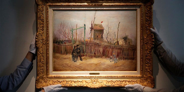 Sotheby's personnel display «Scene de rue à Montmartre» (Street scene in Montmartre), a painting by Dutch master Vincent van Gogh at Sotheby's auction house in Paris, Thursday, Feb. 25, 2021. (AP Photo/Christophe Ena)
