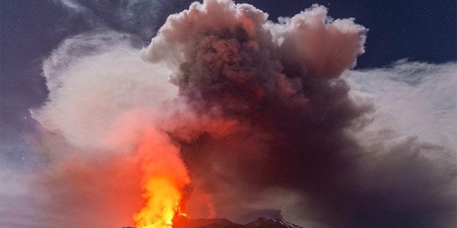 Glowing lava is seen from the north-east side of the Mt Etna volcano engulfed with ashes and smoke near Milo, Sicily, Wednesday night, Feb. 24, 2021. (AP Photo/Salvatore Allegra)