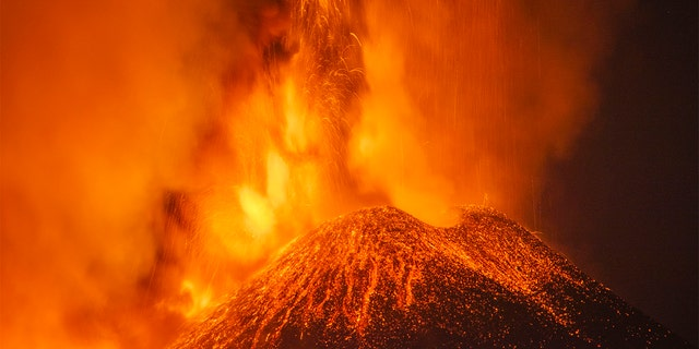 Lava and smoke are belched out from a crater as seen from the north-east side of the Mt Etna volcano near Milo, Sicily, Wednesday night, Feb. 24, 2021. (AP Photo/Salvatore Allegra)