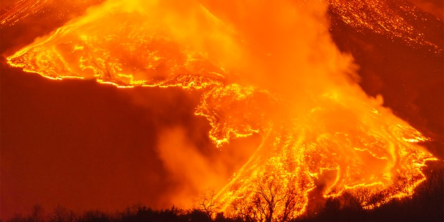 A fiery river of glowing lava flows on the north-east side of the Mt Etna volcano near Milo, Sicily, Wednesday night, Feb. 24, 2021. (AP Photo/Salvatore Allegra)