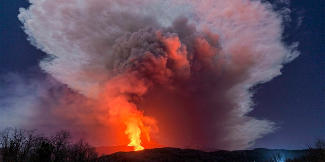 A fiery river of glowing lava flows on the north-east side of the Mt Etna volcano engulfed with ashes and smoke near Milo, Sicily, Wednesday night, Feb. 24, 2021. (AP Photo/Salvatore Allegra)