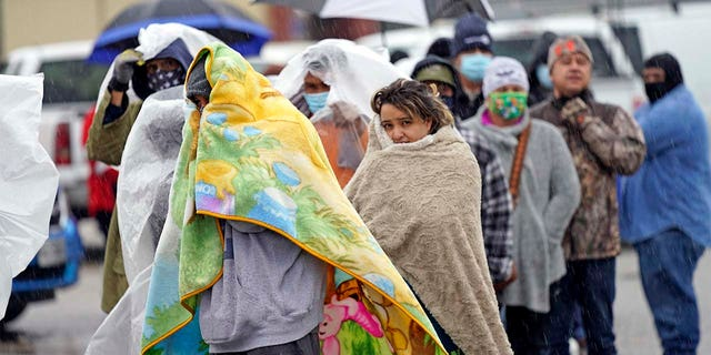 Customers waited over an hour in the freezing rain to fill their tanks. (AP Photo/David J. Phillip)