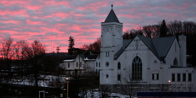 The sky lights up at dawn behind First Presbyterian Church and the rail yard in the historic coal city of Bluefield, W.Va, on Saturday, Jan. 24, 2021. (AP Photo/Jessie Wardarski)