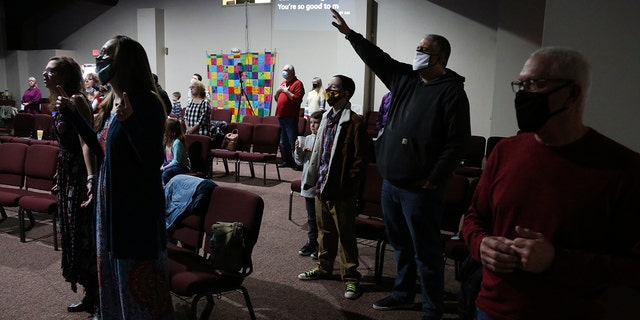 Travis Lowe, second from right, pastor of Crossroads Church in Bluefield, W.Va., raises his arm during services Sunday Jan. 23, 2021. Lowe, who has expressed concern over the divisiveness of American politics, believes collaboration by churches will help heal his town and the country. (AP Photo/Jessie Wardarski)