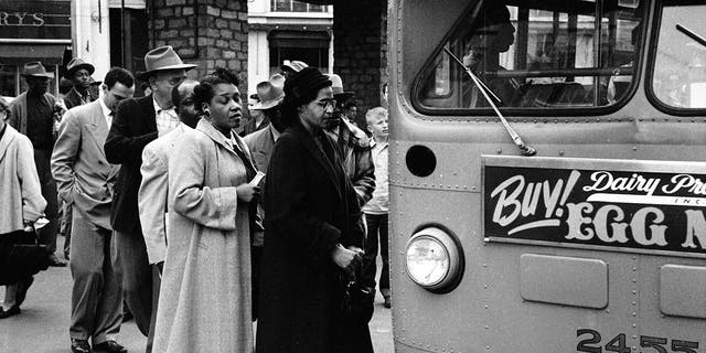American civil rights activist Rosa Parks (센터, in dark coat and hat) waits to board a bus at the end of the Montgomery bus boycott, Montgomery, 앨라배마, 12 월. 26, 1956.
