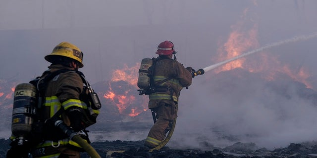 Firefighters battle a fire at a commercial yard in Compton, Calif., on Feb. 26, 2021. (AP Photo/Ringo H.W. Chiu)