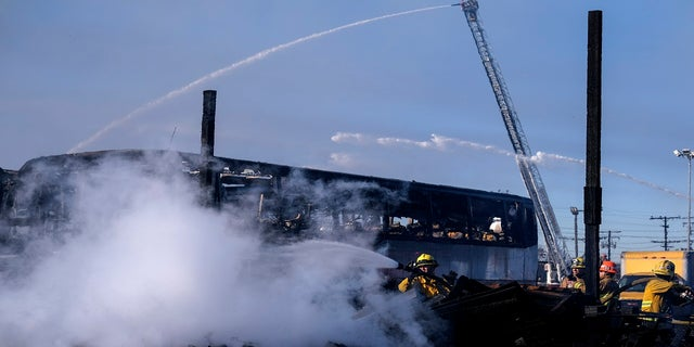 Firefighters battle a fire at a commercial yard in Compton, Calif. on Feb. 26, 2021. (AP Photo/Ringo H.W. Chiu)