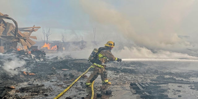 A firefighter battles a fire at at commercial yard in Compton, Calif., on Feb. 26, 2021. (AP Photo/Ringo H.W. Chiu)