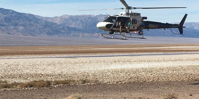 A California Highway Patrol helicopter is shown returning to the staging area after dropping off Inyo County search-and-rescue team members in Deimos Canyon. (NPS)