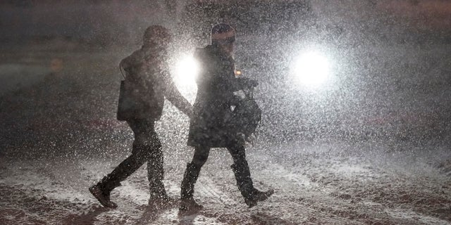 Pedestrians cross a street in Denver as heavy snowfall swept over the region Wednesday night. (AP)