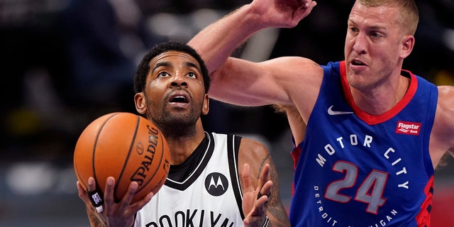 Brooklyn Nets guard Kyrie Irving (11) attempt a layup as Detroit Pistons center Mason Plumlee (24) defends during the first half of an NBA basketball game, Tuesday, Feb. 9, 2021, in Detroit. (AP Photo/Carlos Osorio)
