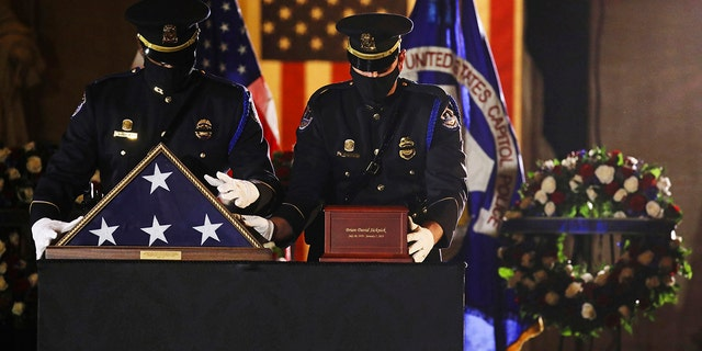 An honor guard places an urn with the cremated remains of U.S. Capitol Police officer Brian Sicknick and folded flag on a black-draped table at center of the Capitol Rotunda to lie in honor Tuesday, Feb. 2, 2021, in Washington. (Leah Millis/Pool via AP)