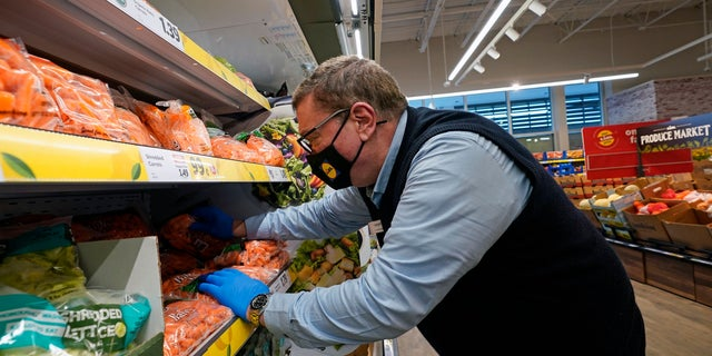 In this Thursday, Feb. 4, 2021 photo, Joseph Lupo, an employee of the grocery chain Lidl, arranges carrots in the produce aisle at the grocery market where he works in Lake Grove, N.Y., after getting vaccinated against coronavirus earlier in the day.