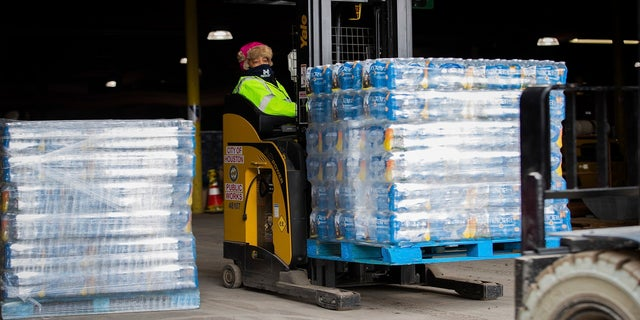 A worker transports bottles of water from the City of Houston Upper Braes Warehouse to delivery trucks on Thursday. (AP/Houston Chronicle)