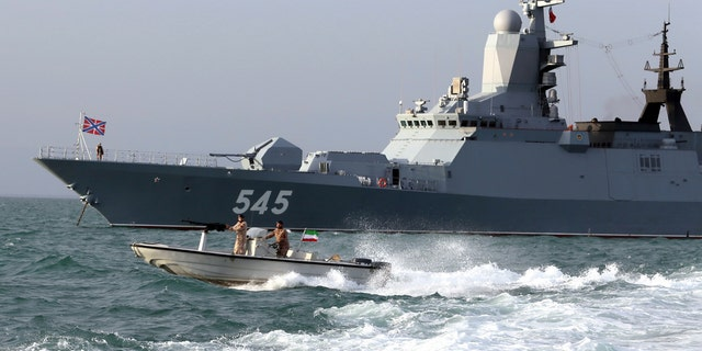A Russian warship and an Iranian army speed boat attend a joint naval exercise on Tuesday. (AP/Iranian Army)