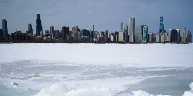Lake Michigan is shown here Sunday covered with snow and ice, with the Chicago skyline in the background. The area is expected to get more than a foot of snow by the end of Tuesday. (AP)