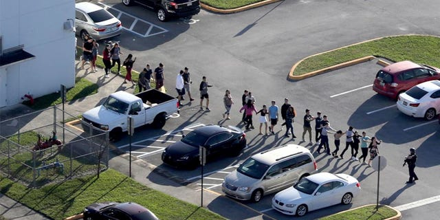 Students are evacuated by police from Marjory Stoneman Douglas High School in Parkland, Fla., during the shooting that took place there in February. (AP/South Florida Sun-Sentinel)