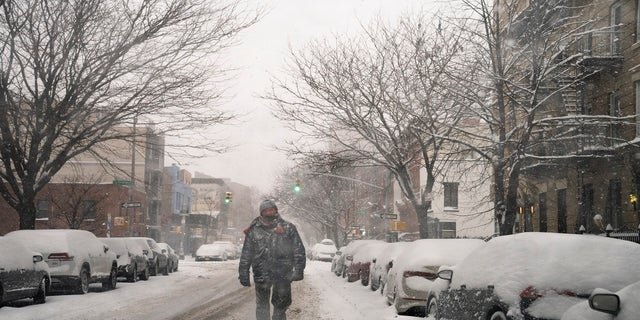 A pedestrian walks down a snow covered street in the Brooklyn borough of New York City on Monday. (AP)