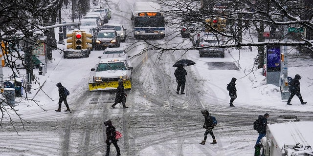 Pedestrians cross roads as snow falls Thursday in the Queens borough of New York City (AP)