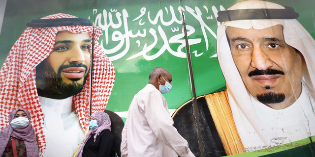 People wear face masks to protect against the spread of the coronavirus in front of a banner showing Saudi King Salman, right, and his Crown Prince Mohammed bin Salman, outside a mall in Jeddah, Saudi Arabia, on Friday, Feb. 5. (AP)