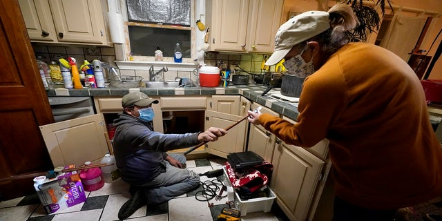 Handyman Roberto Valerio, left, hands homeowner Nora Espinoza a broken pipe after removing it from beneath her kitchen sink on Saturday in Dallas. The pipe broke during freezing temperatures brought by last week's winter weather. (AP)