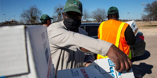 People collect water at a distribution site Tuesday after winter weather caused electricity, blackouts and water service disruption in Dallas.