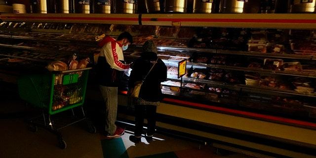 Customers use the light from a cellphone to look in the meat section of a grocery store Tuesday, Feb. 16, 2021, in Dallas. Even though the store lost power, it was open for cash-only sales.