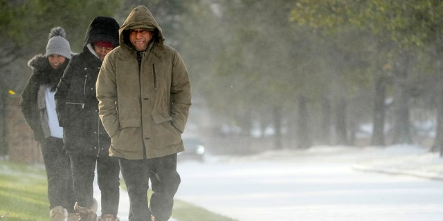 Erasmo Vazquez, right, walks along a snow covered sidewalk with his wife, Maria, center, and daughter Day, left, Monday, Feb. 15, 2021, in Houston.