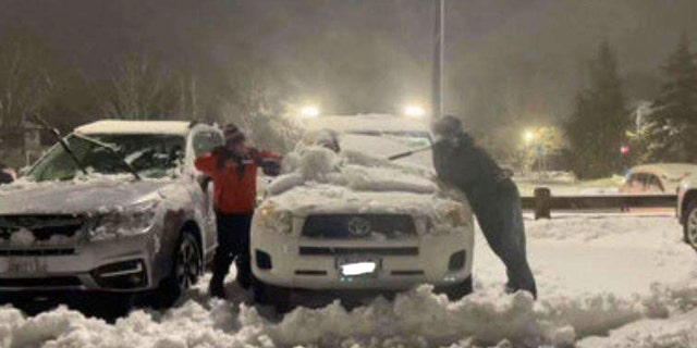 Abbey Meeker and Christian Stone shoveling out cars at Westerly Hospital in Rhode Island on Jan 1, 2020. (Courtesy WJAR)