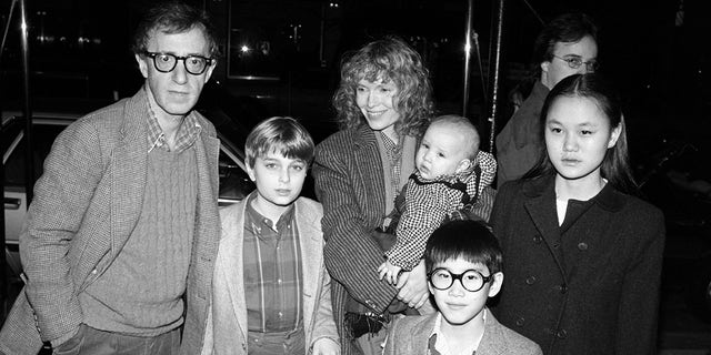 American comedian, actor and film director Woody Allen (left) and his partner, actress Mia Farrow, pose under a canopy with their children, from left Misha, Dylan (in Farrow's arms), Fletcher and Soon Yi, New York, New York, 1986. Soon-Yi later married Allen.  The man in the background has not been identified.