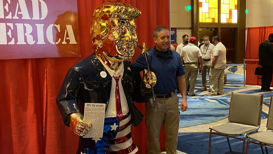 Gold-colored Trump statue at CPAC draws crowd