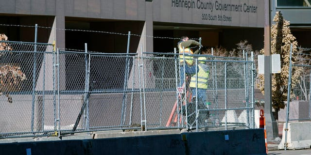 Workers install barbed wire on fencing outside the Hennepin County Government Center, Wednesday, Feb. 23, 2021 in Minneapolis, as part of security preparation for the trial of former Minneapolis police officer Derek Chauvin.