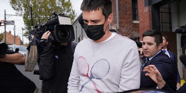Richard Pusey, the driver of a Porsche who allegedly fled the scene of a truck crash on Melbourne's Eastern Freeway which killed four police officers, is taken away from his Fitzroy property by police in Melbourne, Thursday, April 23, 2020. (AAP Image/Michael Dodge)