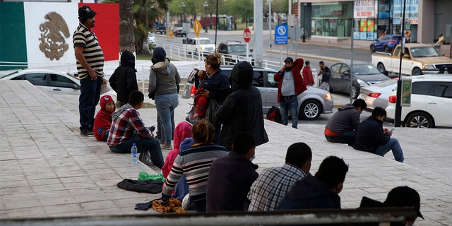 Migrants recently expelled from the U.S. after trying to seek asylum sit next to the international bridge in the Mexican border city of Reynosa, Saturday, March 27, 2021. (AP Photo/Dario Lopez-Mills)