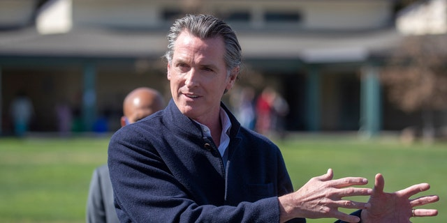 California Gov. Gavin Newsom speaks about the state's plan to reopen schools as coronavirus vaccinations continue during a news conference on the school yard at Barron Park Elementary in Palo Alto, Calif., Tuesday, March 2, 2021. (Karl Mondon/Bay Area News Group via AP)