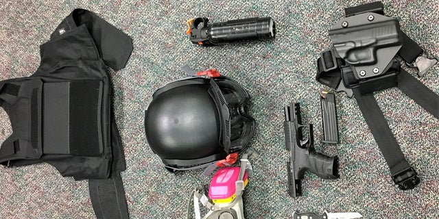 Numerous items left behind by people inside the perimeter of a march, including a crowbar, hammers, bear spray, slugging weapon with rocks, high impact slingshot, and knives, after they corralled a group of about 100 hundred protesters Friday night in Portland, Ore. (Portland Police Department via AP)